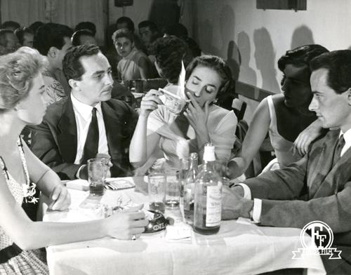 """Χαρακτηριστική σκηνή από το """"Τελευταίο Ψέμα"""", η Έλλη Λαμπέτη χρησιμοποιεί ένα χαρτονόμισμα για τσιγάρο"""