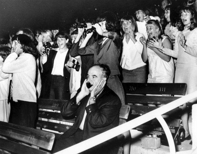 Ένας άντρας κλείνει τα αυτιά του ενώ 18.000 θαυμάστριες ουρλιάζουν στην συναυλία των The Beatles στην Καλιφόρνια, 23 Αυγούστου 1964